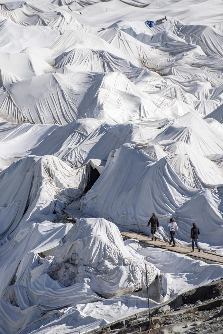 epa08553195 People visit the Rhone Glacier covered in blankets above Gletsch near the Furkapass in Switzerland, 18 July 2020. The Alps oldest glacier is protected by special white blankets to prevent it from melting.  EPA/URS FLUEELER