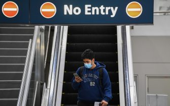 SYDNEY, AUSTRALIA - JULY 07: A man wearing a face mask looks at his phone as he arrives at Sydney Airport on one of the last flights out of Melbourne to Sydney on July 07, 2020 in Sydney, Australia. The NSW-Victoria border will close at 11:59pm on Tuesday evening due to a large spike in COVID-19 cases in Victoria. It is the first time in 100 years the border between the two states has been closed, and comes after Victoria recorded its highest-ever daily increase in cases, 127, since the start of the pandemic on Monday, along with the deaths of two Victorian men. From 12:01 Wednesday 8 July, NSW residents returning from Victoria will need to self isolate for 14 days. Special provisions will be in place for border communities such as Albury-Wodonga as well as freight operations and other critical services. (Photo by James D. Morgan/Getty Images)