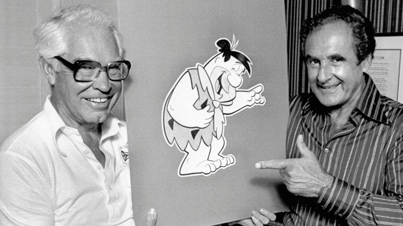 "The creators of ""The Flintstones,"" the popular animated series, hold up a drawing of Fred Flintstone."