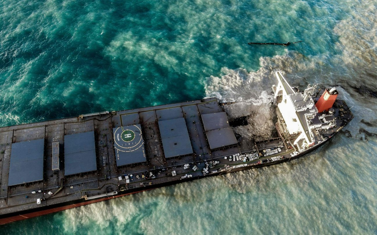 An aerial view taken on August 15, 2020 shows the vessel MV Wakashio, belonging to a Japanese company but Panamanian-flagged that had run aground near Blue Bay Marine Park, Mauritius three weeks ago. - A fresh streak of oil spilled on August 14, 2020, from a ship stranded on a reef in pristine waters off Mauritius, threatening further ecological devastation as demands mount for answers as to why the vessel had come so close to shore. (Photo by STRINGER / AFP) / The erroneous mention[s] appearing in the metadata of this photo by STRINGER has been modified in AFP systems in the following manner: Source IPTC should read [AFP] instead of [L'Express Maurice]. Please immediately remove the erroneous mention[s] from all your online services and delete it (them) from your servers. If you have been authorized by AFP to distribute it (them) to third parties, please ensure that the same actions are carried out by them. Failure to promptly comply with these instructions will entail liability on your part for any continued or post notification usage. Therefore we thank you very much for all your attention and prompt action. We are sorry for the inconvenience this notification may cause and remain at your disposal for any further information you may require. (Photo by STRINGER/AFP via Getty Images)