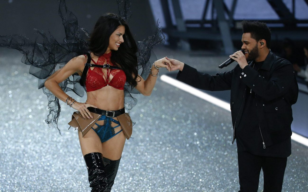 epa05654260 Brazilian model Adriana Lima (L) takes to the catwalk as Canadian singer The Weeknd performs (R) during the 2016 Victoria's Secret Fashion Show at the Grand Palais in Paris, France, 30 November 2016. EPA/IAN LANGSDON