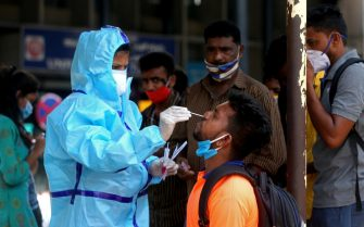 epa09155086 A health worker takes a nasal swab sample of a man for COVID-19 test at the city railway station in Bangalore, India, 23 April 2021. The Karnataka government is contemplating a partial lockdown of the city in the wake of rising Covid-19 cases, extending the night curfew and imposed a weekend curfew which includes closure of cinema halls, bars and pubs, gyms and colleges. India recorded a massive surge of 332,730 fresh Covid-19 cases and 2263 deaths, the highest single-day spike in COVID-19 infections. EPA/JAGADEESH NV